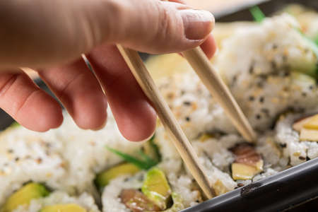 Woman eating salmon, avocado and mango inside out California sushi with wooden chopsticks from take away Bento box