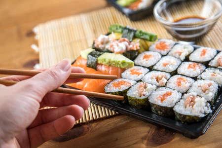 Woman eating salmon Nigiri and maki sushi bento with chopsticks 스톡 콘텐츠