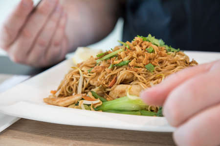 Man eating Chinese fried noodels with chicken, onions, coriander and Pak Choi in Restaurant
