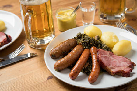 Oldenburger green cabbage with sausage mix, Kassler pork neck, boiled potatoes, mustard, beer and grain liquor is an traditional German winter dish