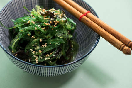 Japanese Wakame seaweed salad with sesame seeds with chopsticks in bowl