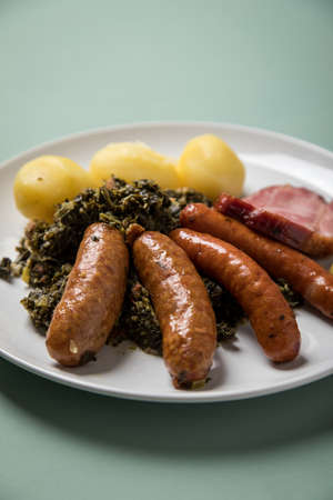 Oldenburger green cabbage with sausage mix, Kassler pork neck, boiled potatoes and mustard is an traditional German winter dish