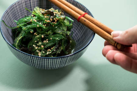 Woman eating Japanese Wakame seaweed salad with sesame seeds with chopsticks Imagens