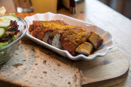 German gourmet currywurst grilled and sliced sausage with curry ketchup, salad and slice of rustic bread on wooden board in restaurant