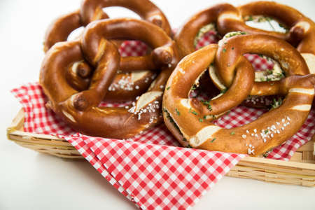 German soft Brezel pretzel with salt, chives and butter in bread basket Standard-Bild