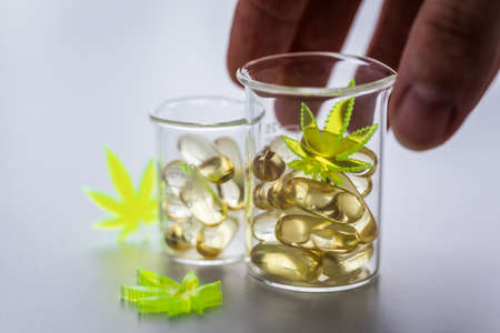 Woman using pills, tablets, capsules of cannabis marijuana hemp and CBD in lab scale glass beaker as pain killer
