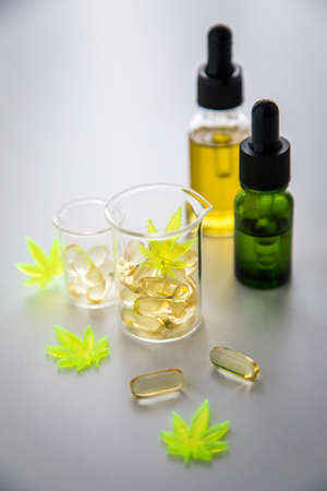 Pills, tablets,  capsules and oil of cannabis marijuana hemp and CBD in lab scale glass beaker as pain killer and medical
