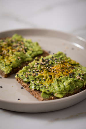 Avocado, sesame and turmeric on sunflower seed whole grain bread slice for breakfast or snack on marble background