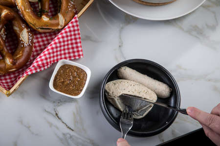Man eats Munich white sausage with knife and fork, sweet mustard and pretzel and take off sausage properly out of gut Stock Photo
