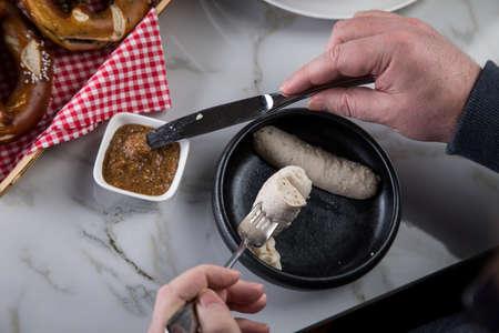 Mann isst Münchner Weißwurst mit Messer und Gabel, süßen Senf und Brezel und nimmt Wurst richtig aus dem Darm