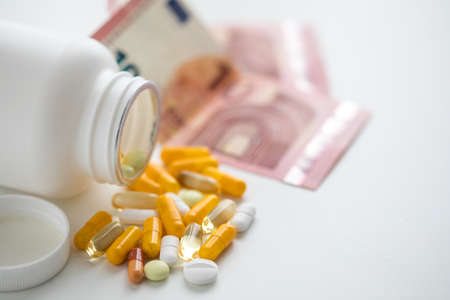 Money bills for pill compartment with white and yellow pills, tablets and capsule medicine