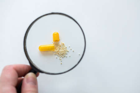 Magnifying glass controlling yellow pill tablet capsule for medicine side effects and ingredients