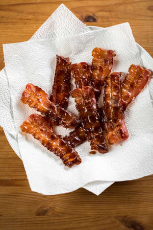 Crispy fried bacon rashers draining on plate with napkin on wooden table background 写真素材