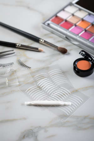Eye shadow palette, brushes, fake lashes, tweezers and artificial eyelid crease double tapes for eye makeup on marble beauty desk table