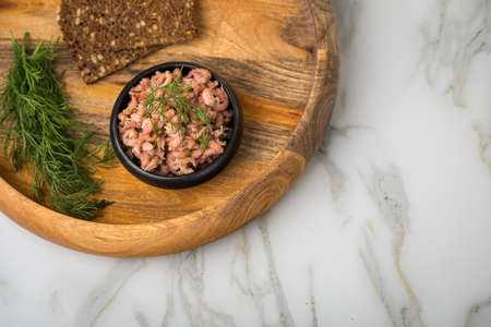 Peeled German Friesland north sea shrimps or crabs in bowl on wooden and marble background