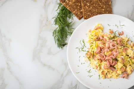 German Friesland north sea shrimps with scrambled eggs, whole grain bread and dill on marble background Stock Photo