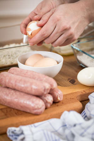 Woman peeling egg for Scotch Eggs in sausage pork meat and breadcrumbs as party food