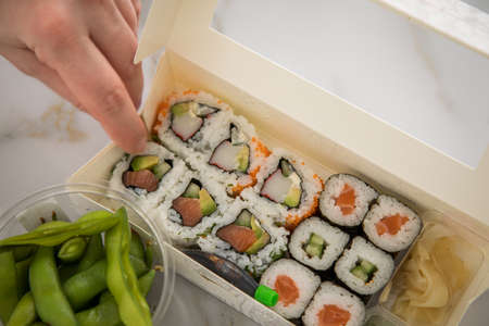 Woman eating edamame, salmon, surimi, cucumber and avocado Maki and inside out California sushi with soy sauce, pickled ginger, wasabi and soy sauce in take away tray Bento box