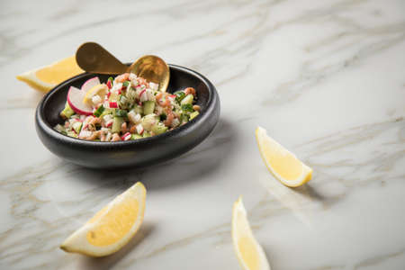 German Friesland north sea brown shrimps salad in bowl with cucumber, red radish, dill and lemon on marble table