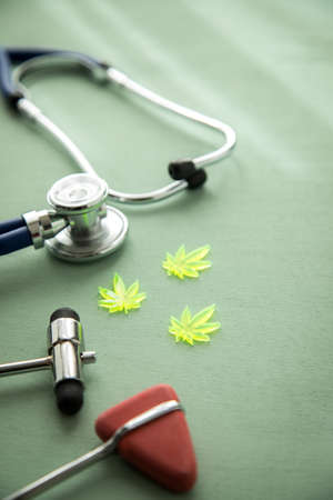 Cannabis marijuana hemp CBD as pain killer or medical therapy at neurologist doctors office with reflex hammer and stethoscope Imagens