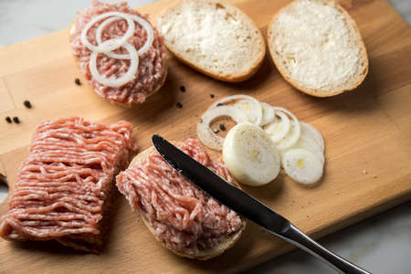 German snack bread roll buns with raw minced pork meat, butter, pepper and onion rings on wooden board and marble counter top