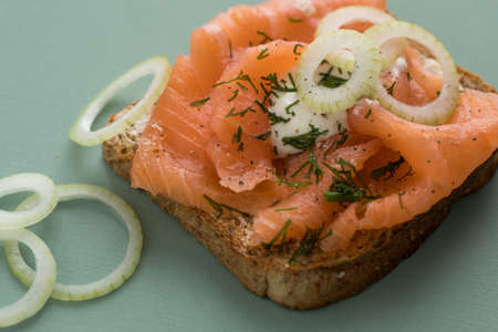 Smoked salmon on whole grain toast with onion rings, dill and horseradish on wooden board