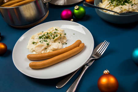 Wiener sausages and potato salad as typical German Christmas eve holiday dinner with tree decoration and ornaments