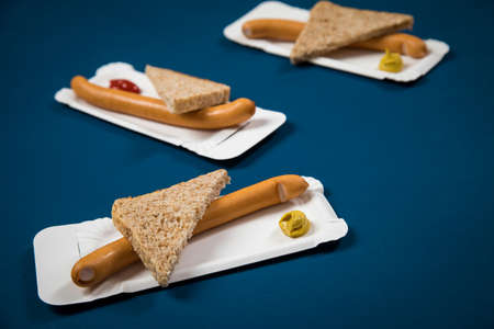 Wiener sausages with whole grain bread slice on disposable paper plate with mustard and ketchup on blue background