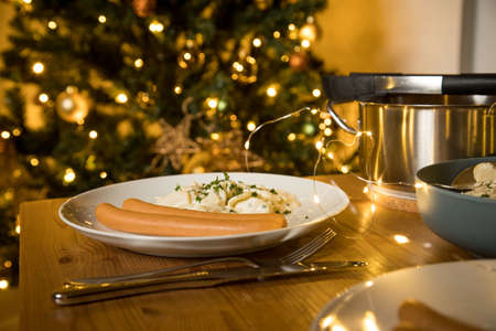 Wiener sausages and potato salad as typical German Christmas eve holiday dinner with decorated Christmas tree and fairy lights on wooden table 写真素材