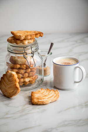 Italian puff pastry fan wavers cookies biscuits with preserving glass jar and cup of coffee on marble table background Imagens