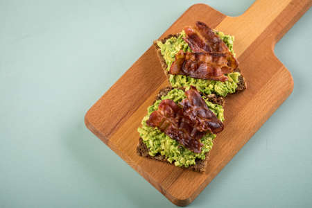 Avocado bacon on sunflower seed whole grain bread slice for breakfast or snack