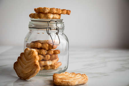 Italian puff pastry fan wavers cookies biscuits with preserving glass jar on marble table background Stock Photo
