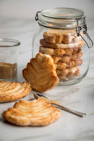 Italian puff pastry fan wavers cookies biscuits with preserving glass jar and brown sugar on marble table background