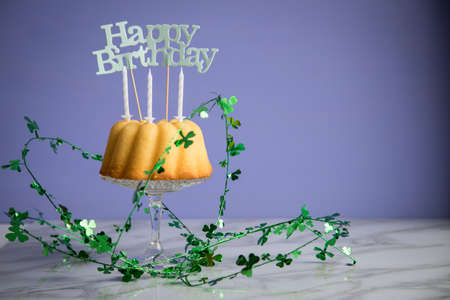 Happy birthday ring cake with clover decoration on marble table and lilac background