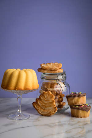 Gugelhupf ring cake, muffins, Italian puff pastry fan wavers cookies biscuits as selection buffet on marble table and lilac background Stock Photo