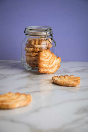 Italian puff pastry fan wavers cookies biscuits with preserving glass jar on marble table and lilac background