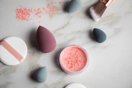Loose rouge make-up powder with blender, sponge and brush on marble beauty table Stock Photo