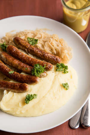Small fried Bavarian German Nürnberger sausages with sauerkraut, mashed potatoes and mustard on wooden table background