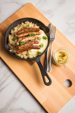 Small fried Bavarian German Nürnberger sausages with sauerkraut, mashed potatoes and mustard in iron cast pan on marble table