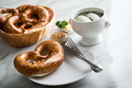 German Weißwurst white sausage in porcelain pot, Bavarian sweet mustard, butter and pretzel on marble table Stock Photo
