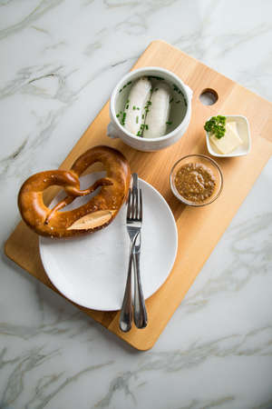 German Munich Weißwurst white sausage in porcelain pot, Bavarian sweet mustard, butter and pretzel on wooden cutting board Stock Photo