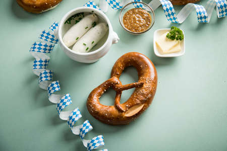 German Munich Weißwurst white sausage in porcelain pot, Bavarian sweet mustard, butter and pretzel with Oktoberfest streamers on pastel green background