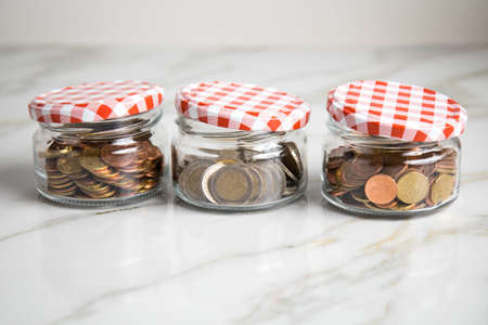 3 glass jars of loose cash and 2€ coins for housekeeping money, vacation or saving goals