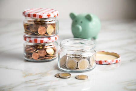 Piggy bank, 3 glass jars of loose cash and 2 Euro coins for housekeeping money and vacation or saving goals
