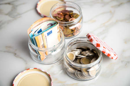 3 glass jars with Euro notes, 2€ coins and loose cash for housekeeping and savings