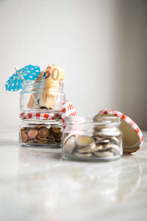 3 glass jars with Euro notes, sunshade, 2€ coins and loose cash for housekeeping and vacation savings