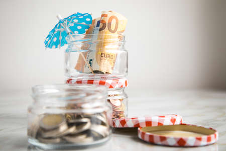 3 glass jars with Euro notes, sunshade, 2€ coins and loose cash for housekeeping and vacation savings Stock Photo