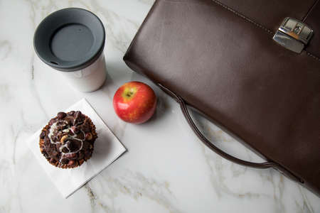 Hazelnut muffin, coffee in to go mug and apple as breakfast on the way to work with leather briefcase on marble table