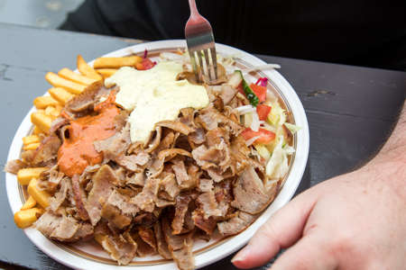 Man eating German Döner Kebab dish with veal, salad, French fries hot sauce and herb sauce