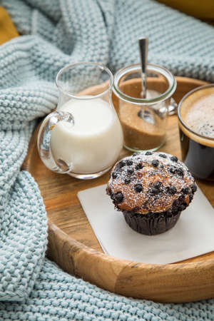 Blueberry muffin with coffee, sugar and milk on wooden tray and comfy sofa with blue wool knit blanket and yellow cushions